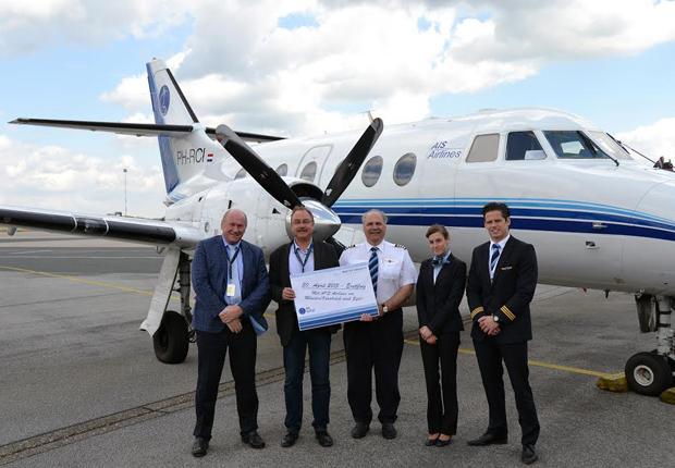 Das Foto zeigt AIS-Vertriebsdirektor Harry van Lieshout (l.) und Detlef Döbberthin (2.v.r) aus der FMO-Marketingabteilung mit der Crew des Erstfluges. (Foto: FMO Flughafen Münster/Osnabrück GmbH)