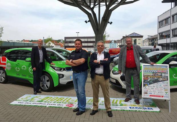 """Stadtwerke-Vorstand Dr. Stephan Rolfes sowie Bernd Stegmann, Organisationsleiter im MSC Osnabrück e.V. drücken den beiden Fahrern Holger Maes (BMW i3) sowie Peter Schaar (Opel Ampera) für den 1. Wertungslauf zum """"E-Mobil-Berg-Cup"""" im Rahmen des 20. Ibergrennens die Daumen. (Foto: Stadtwerke Osnabrück AG)"""