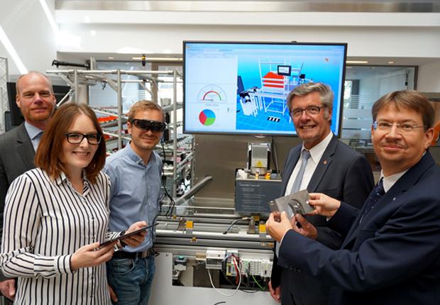 Montageunterstützung durch 3D-Brillen, Steuerung über das Tablet und intelligente Anpassung von Maschinen. In der SmartFactoryOWL erläutert Prof. Dr. Volker Lohweg (Hochschule OWL, 1. von rechts) Klaus Peter Jansen (it's OWL Clustermanagement), Marina Römhild (TU Dortmund), Sten Döhler (Sächsisches Textilforschungsinstitut) und Landrat Friedel Heuwinkel (v.l.n.r.), wie die Fabrik der Zukunft funktioniert. (Foto: CIIT)