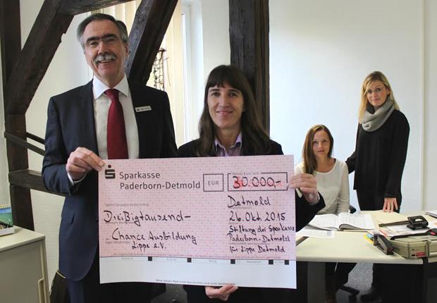 Wichtige Unterstützung: Hans Laven (links), Vorsitzender des Vorstandes der Sparkasse Paderborn-Detmold, übergibt den symbolischen Spendenscheck in Höhe von 30.000 Euro aus Stiftungsmitteln der Stiftung der Sparkasse Paderborn-Detmold für Lippe-Detmold an Cathrin-Claudia Herrmann (2.v.l.), 2. Geschäftsführerin des CAL e.V. Ausbildungsmanagerin Jaqueline Donath (rechts) freut sich gemeinsam mit Auszubildender Susanne Niefert über die großzügige Unterstützung. (Foto: CAL e.V.)