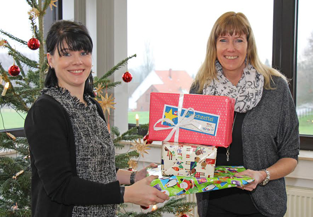 Kleidung und Schuhe, Kosmetik und Schmuck, Bücher, CDs und Spielzeug: Petra Imort (rechts) von Karlsson e. V. nahm die 108 Weihnachtsgeschenke von Vanessa Reimann (links), Marketingassistentin der Buschjost GmbH, entgegen. (Foto: Buschjost GmbH)