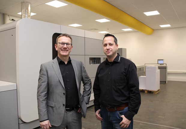 Torsten Bischof (links), Geschäftsführer documenteam und Kai Becker, Vertriebsleiter documenteam vor der neuen Farb-Digitaldruckmaschine, die 300 DIN-A4-Seiten pro Minute produzieren kann. (Foto: documenteam GmbH & Co. KG)