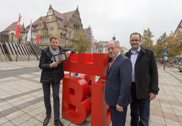 """""""Bielefelds Oberbürgermeister Pit Clausen (Mitte), Martin Knabenreich (r.), Geschäftsführer Bielefeld Marketing, und Marc Detering (l.), Geschäftsführer deteringdesign, stellten den neuen Markenauftritt der Stadt Bielefeld vor."""" (Foto: Björn Schmidt)"""