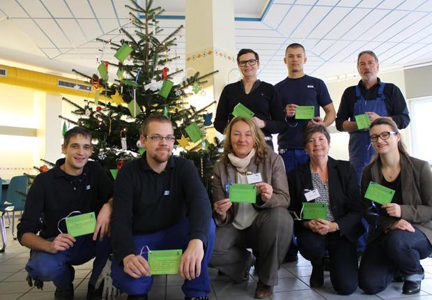 Vom Nikolaus für gut befunden: Christian Nicolaus (ganz links) und weitere Mitarbeiter und Mitarbeiterinnen von B+K sowie Vertreterinnen der Wohngruppen vor dem geschmückten Weihnachtsbaum in der Kantine. (Foto: B+K)