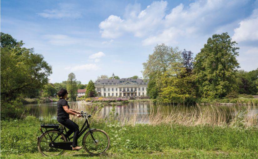 Mit Abstand unterwegs: Auf der 100 Schlösser Route winken imposante Bauwerke von nah und fern, wie hier das Schloss Varlar. Fahrradfahrerin vor Schloss Varlar © Münsterland e.V./Hans Zaglitsch
