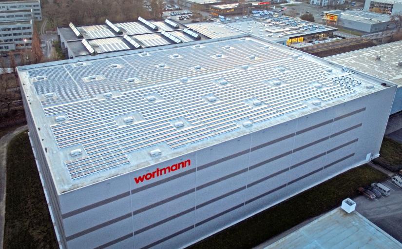 Das Hochregallager mit PV-Anlage (im Vordergrund) und die Hauptverwaltung mit Outlet (Im Hintergrund). - Foto: Wortmann Gruppe